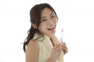 歯ブラシを持つ笑顔の女性