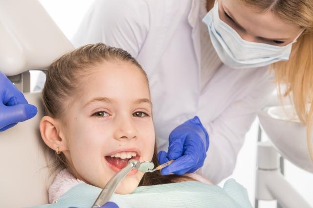 歯医者で治療する子供