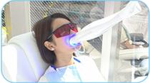ホワイトニング専用のLEDライトを照射する女性